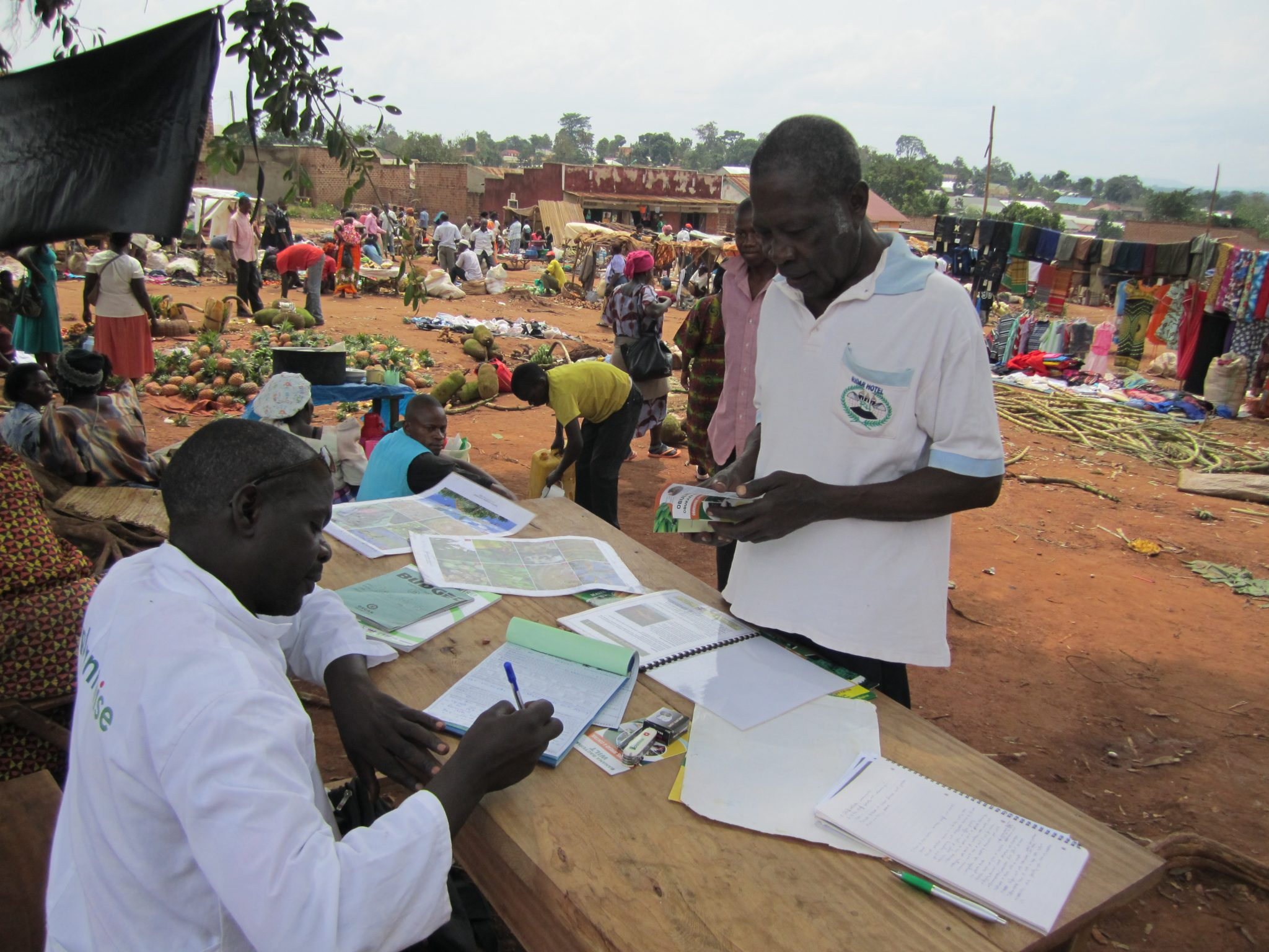 Plant doctor Daniel Lyazi notes a treatment for a farmer in Nakifuma market, Mukono District