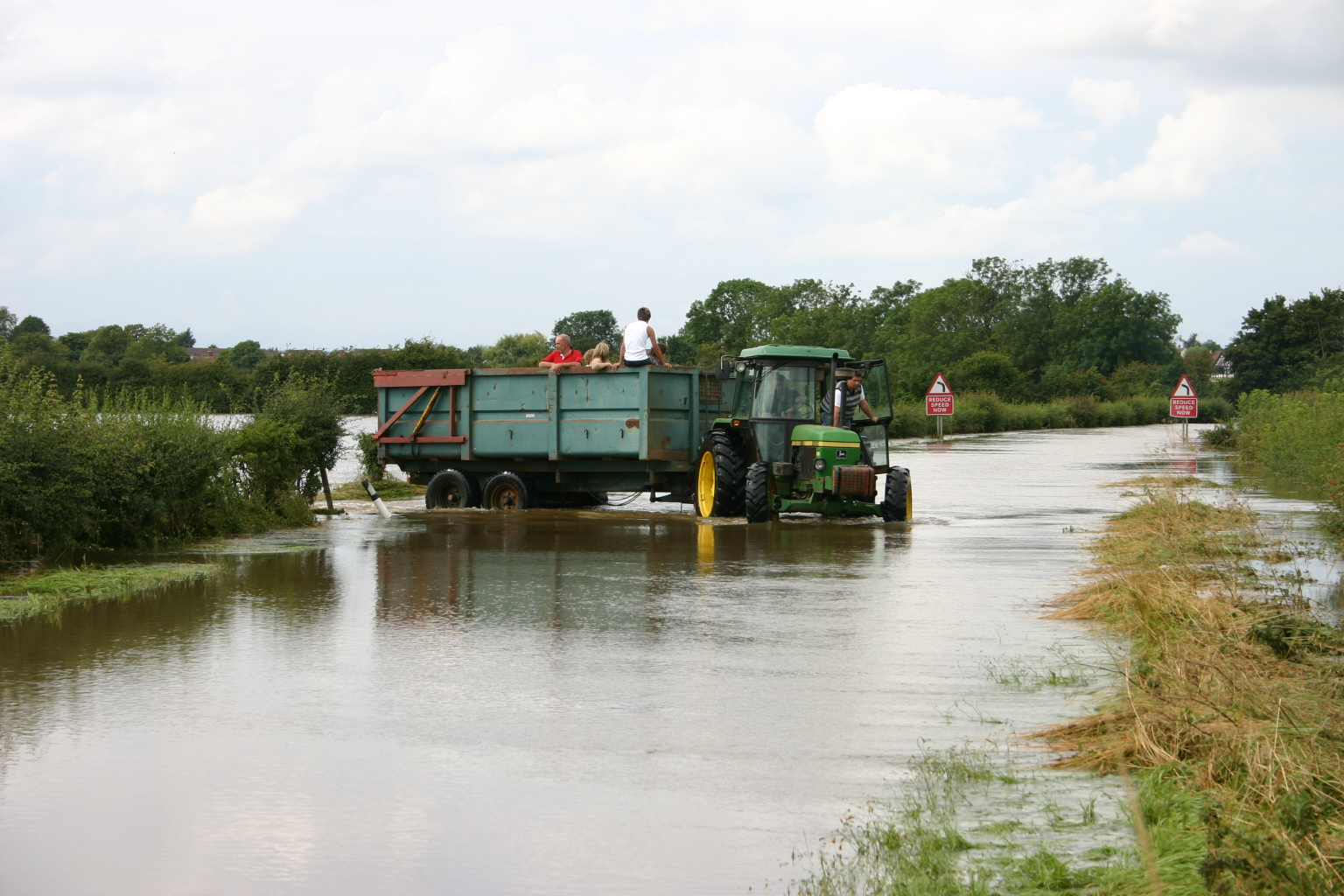 Tractor in moving from a flooded field to a flooded road
