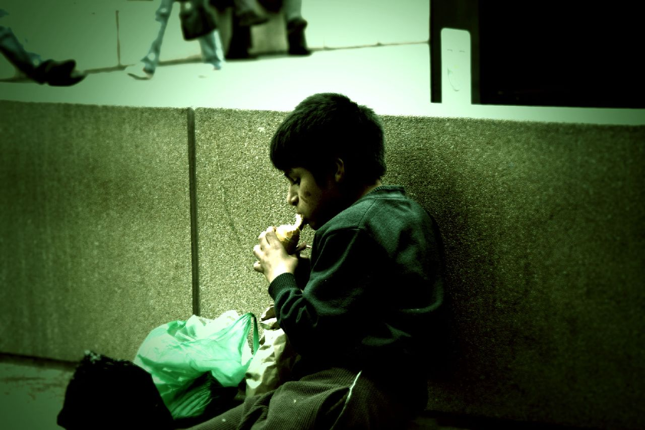 Homeless boy eating food on the street