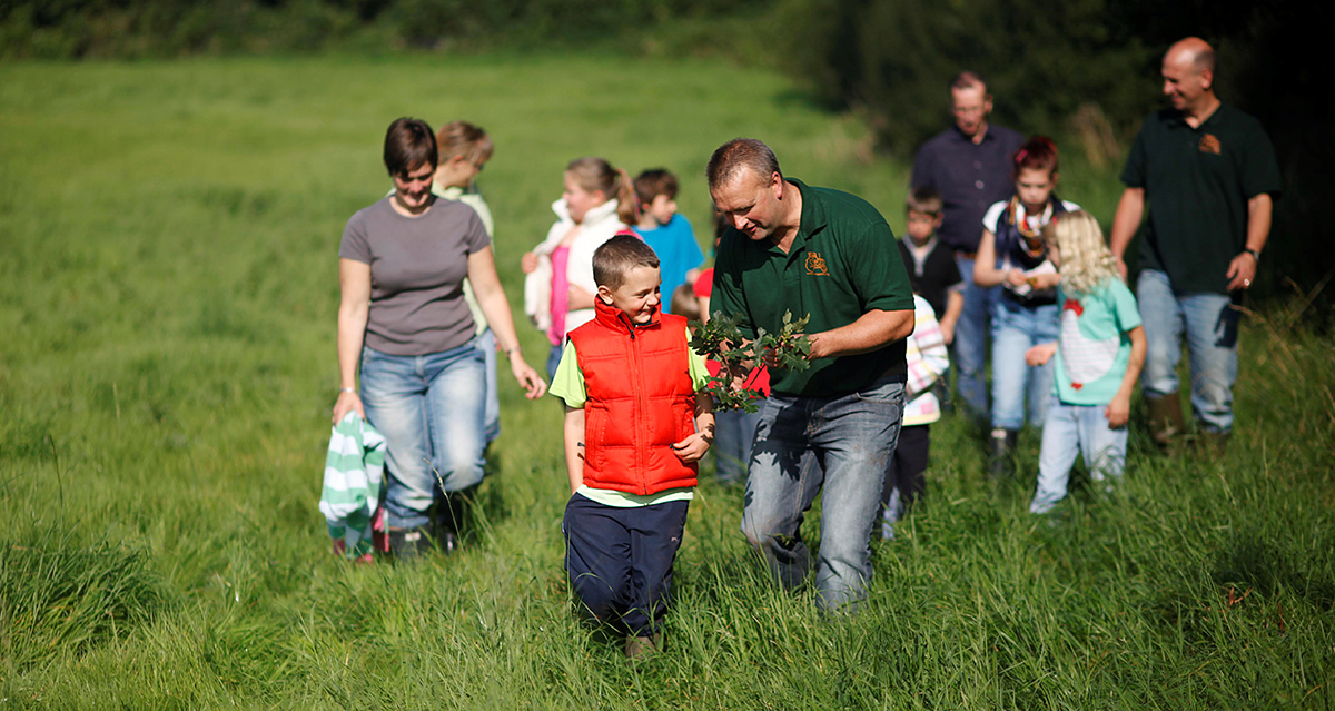 Children and adults in a field on a farm
