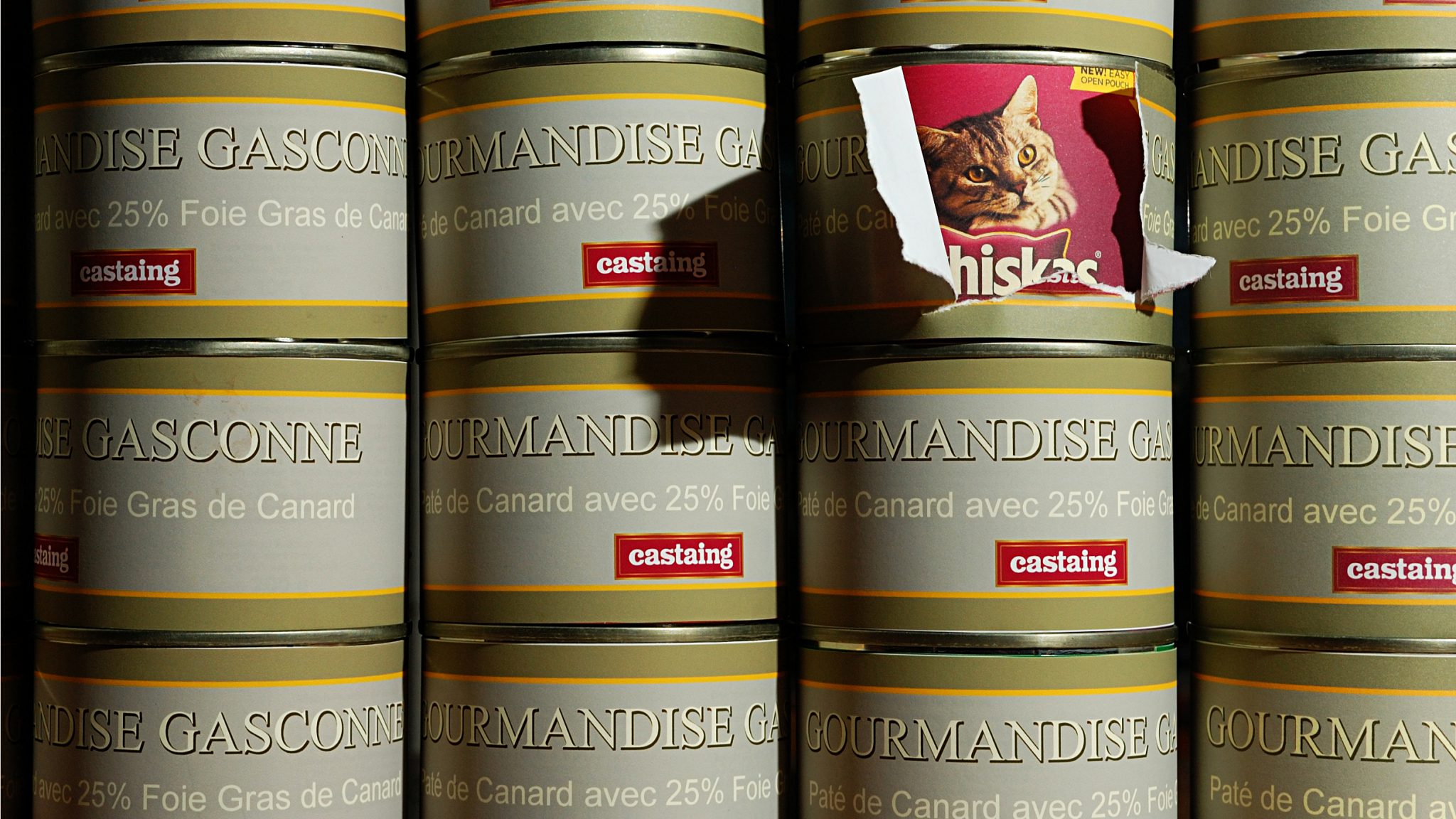 Stack of food cans with one label pealing away to reveal true contents