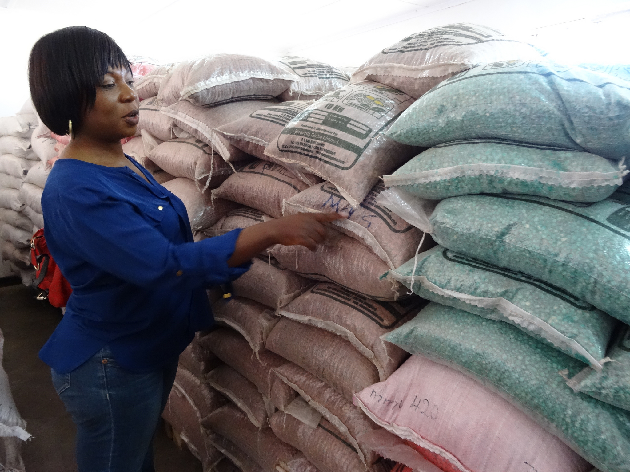 Woman from Zambia next to sacks of food
