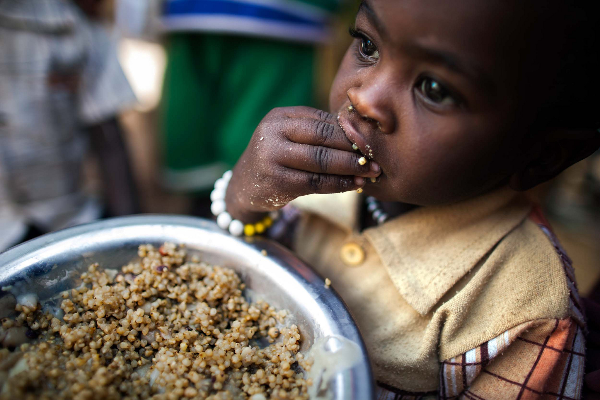A child eats lentils in a food distribution center in the Rwanda camp