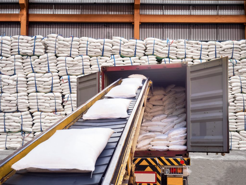 White bags of sugars from warehouse are staffing in container for export