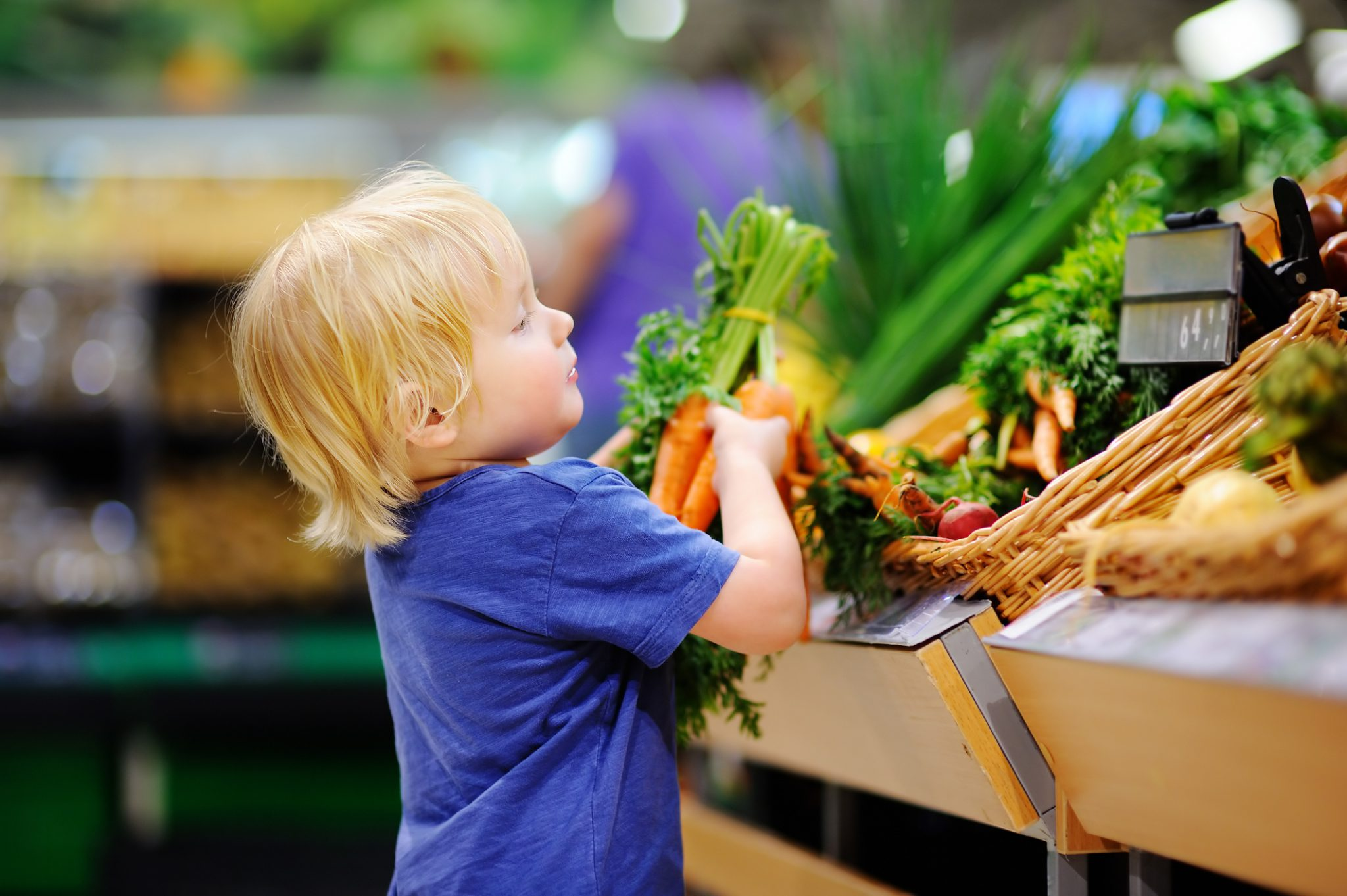 Cute toddler boy in supermarket choosing fresh organic carrots